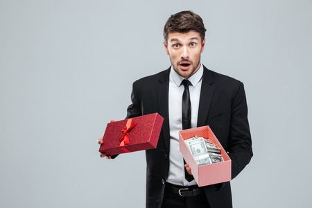 wondered: Surprised young businessman holding opened gift box with money over white background Stock Photo