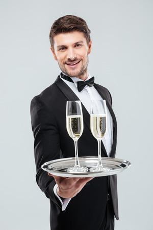 alcohol server: Smiling young waiter in tuxedo offers you glass of champagne