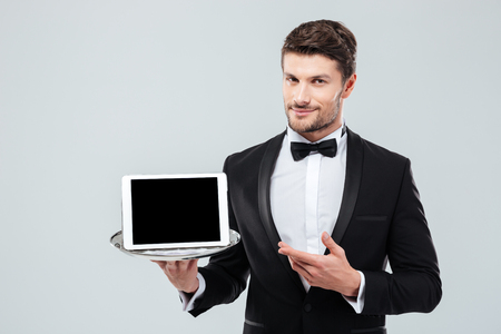 Confident young butler in tuxedo holding and pointing at blank screen tablet on tray Stock Photo