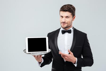Fiducioso giovane Butler in smoking detenzione e che punta a tavoletta schermo in bianco su vassoio