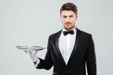 Portrait of young butler in tuxedo holding empty tray Stock Photo