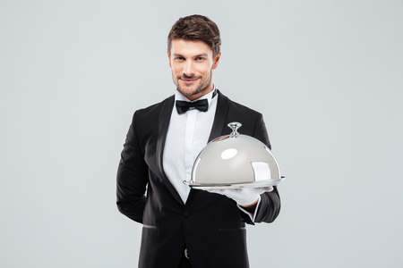food tray: Smiling young butler in tuxedo and gloves holding tray with silver catering dome