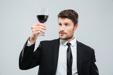 man in suite: Serious young man sommelier in suite tasting red wine in glass over white background