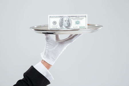 white glove: Hand of waiter in white glove holding tray with dollars