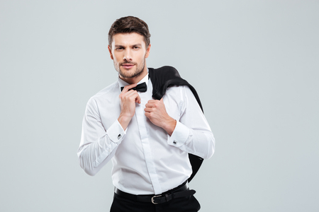 tuxedo jacket: Man in tuxedo with bowtie standing and holding his jacket Stock Photo
