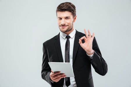 Happy young businessman with tablet winking and showing ok sign over white background Stock Photo