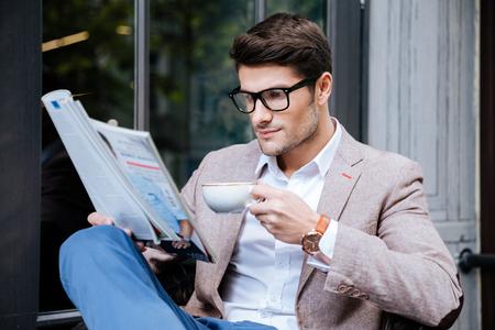 Concentrato giovane in vetri con caffè e la rivista si siede in caffè all'aperto