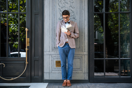 come up to: Young stylish nerd man reading books outdoors Stock Photo