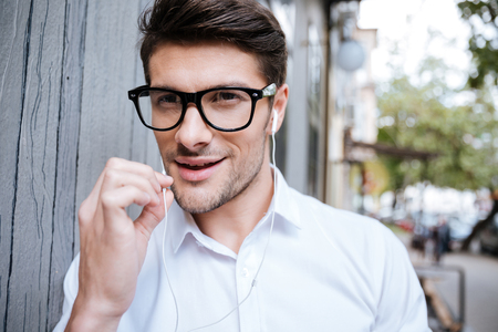 handsfree phone: Handsome young man in glasses walking outdoors and talking on the phone with handsfree Stock Photo