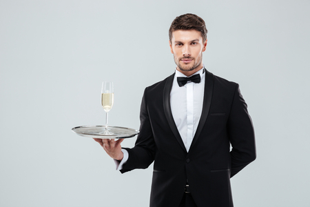 smocking: Portrait of butler in tuxedo and bow tie holding tray with glass of champagne Stock Photo