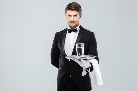Confident young butler in tuxedo and gloves holding glass of water on silver tray