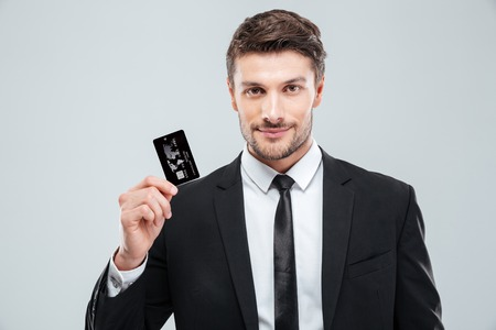 blank space: Portrait of handsome young businessman holding credit card over white background