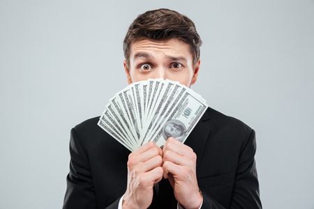 face covered: Confused young businessman covered his face with money over white background