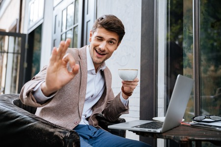 Happy young man showing ok sign and using laptop in outdoor cafe