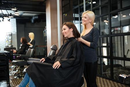 mujeres maduras: Joven muchacha sonriente sentada en el salón de belleza y peluquería femenina hablando con