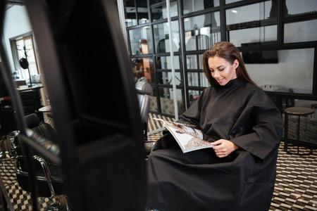 personas leyendo: Hermosa mujer joven sentada en el salón de belleza y la lectura de la revista de moda Foto de archivo