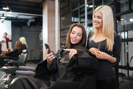 Happy young woman pointing at smartphone and hairdresser making hair styling at salon Stock Photo