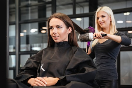 stylist: Young stylist drying woman hair in beauty salon Stock Photo