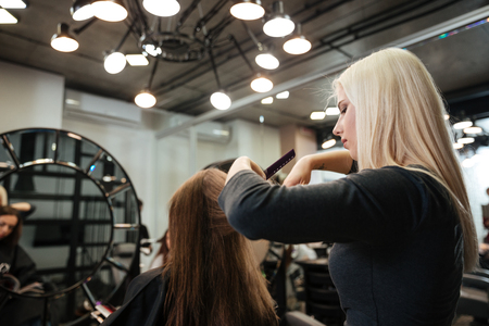 horizontal haircut: Happy young woman getting new haircut by female hairdresser at beauty salon
