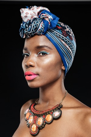 Close-up portrait of a beautiful african woman in shawl on head isolated on the black background