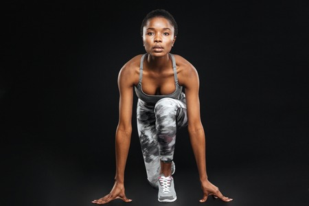 Full length of concentrated beautiful young african american sportswoman over black background Stock Photo