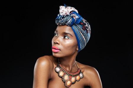 黒い背景に分離先探している美しい若いのアフロ ・ アメリカ人女性のクローズ アップの肖像