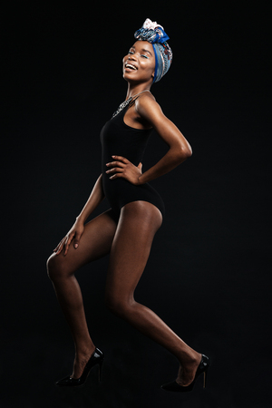 Lovely african woman in bodysuit posing isolated on a black background