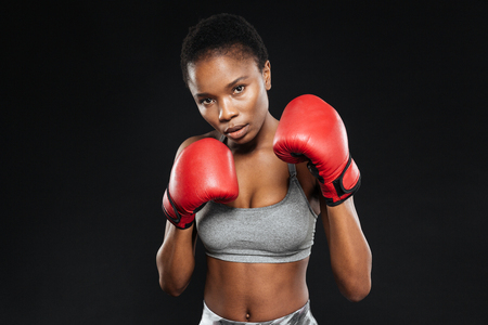 american sport: Fitness pretty girl in boxing gloves fighting on black background Stock Photo