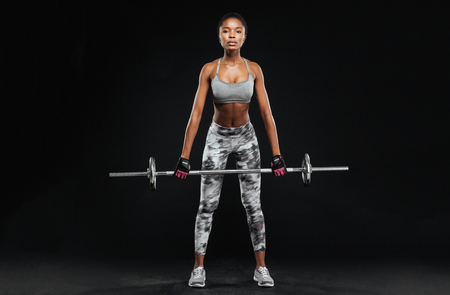 athletic body: Strong young woman with beautiful athletic body doing exercises with barbell isolated on a black background Stock Photo