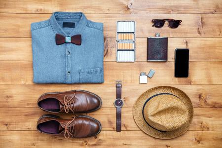 Travel concept shoes, shirt, mobile phone, watch, lighter, flask, eyeglasses, hat on the desk