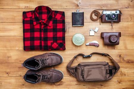 temperino: Travel concept boots, shirt, camera, lighter, flask, bag, penknife on the desk Archivio Fotografico