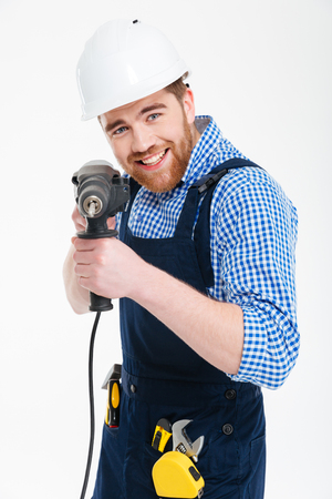 erector: Smiling bearded young man using drill and pointing on you