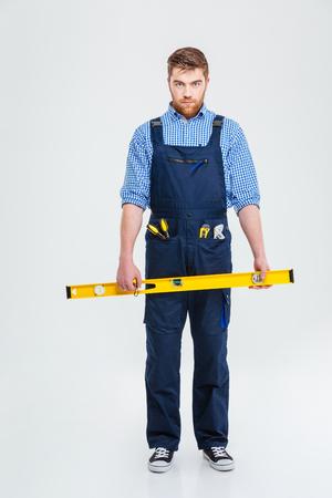 Volledig lengteportret van een ernstige mannelijke die holdingswaterpas van de bouwer en camera bekijken op een witte achtergrond wordt geïsoleerd