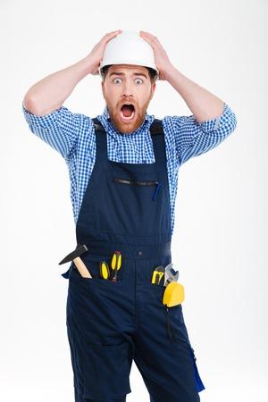 Asombrado conmocionado joven constructor en casco staning con la boca abierta Foto de archivo