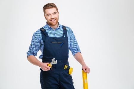 Portret van een gelukkige mannelijke bouwer stond geïsoleerd op een witte achtergrond Stockfoto