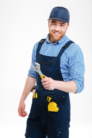 Cheerful bearded repairman in overall and cap standing and holding adjustable wrench