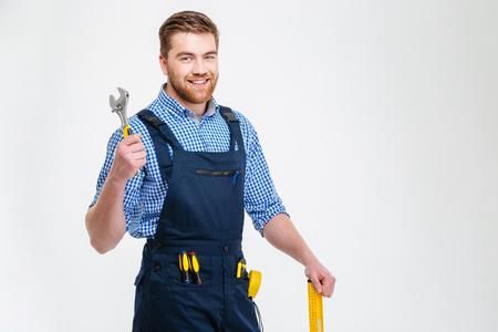 Portret van een glimlachende mannelijke bouwer die zich met materiaal bevindt dat op een witte achtergrond wordt geïsoleerd Stockfoto