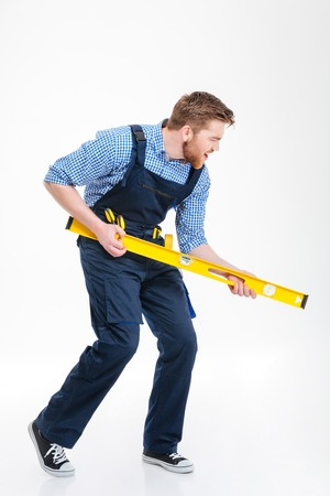 fixer: Full length portrait of a funny male builder posing with waterpas isolated on a white background