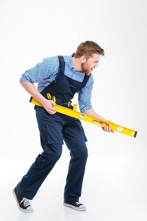 Full length Portret van een grappige man bouwer poseren met waterpas geïsoleerd op een witte achtergrond Stockfoto