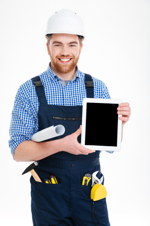 Smiling handsome young builder holding blank screen tablet Stock Photo