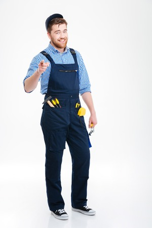 Smiling bearded young man builder in overall and cap pointing on you Фото со стока