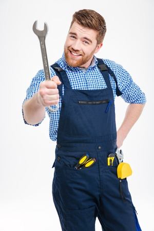 erector: Smiling bearded young man standing and showing wrench Stock Photo
