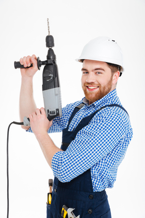 mounter: Happy attractive young worker standing and smiling using drill