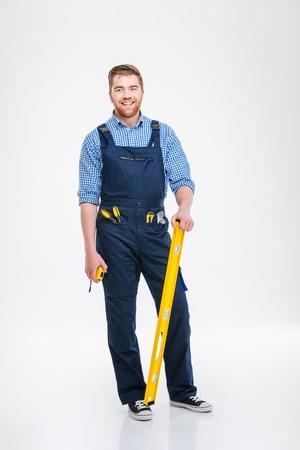 Volledig lengteportret van een glimlachende mannelijke bouwer status geïsoleerd op een witte achtergrond Stockfoto