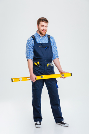 journeyman: Full length portrait of a smiling male builder holding waterpas isolated on a white background