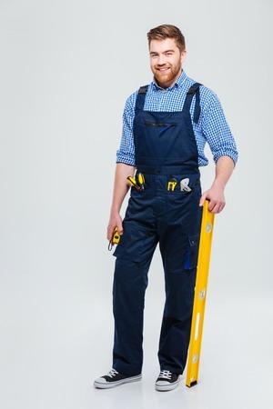 Volledig lengteportret van een knappe mannelijke bouwer status geïsoleerd op een witte achtergrond Stockfoto