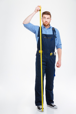 full height: Serious young worker standing and measuring hid growth with yellow tape Stock Photo