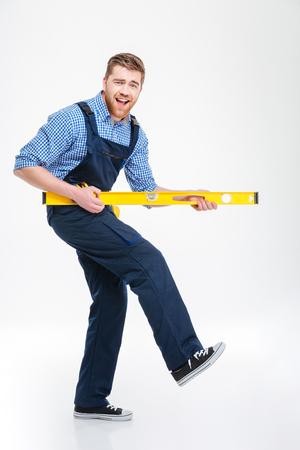 Full length portret van een vrolijke mannelijke bouwer spelen met waterpas geïsoleerd op een witte achtergrond