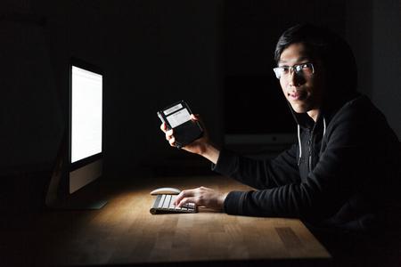 Hacker usando la computadora y robar información del disco duro en la oficina oscura