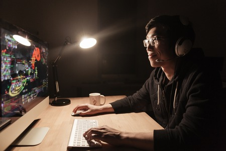 Happy handsome asian male gamer playing computer game at the table in dark room Stock Photo